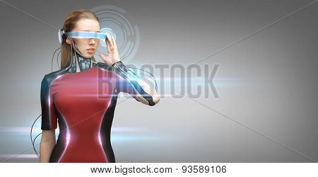 people, technology, future and progress - young woman with futuristic glasses and microchip implant or sensors over gray background with virtual projection and laser light