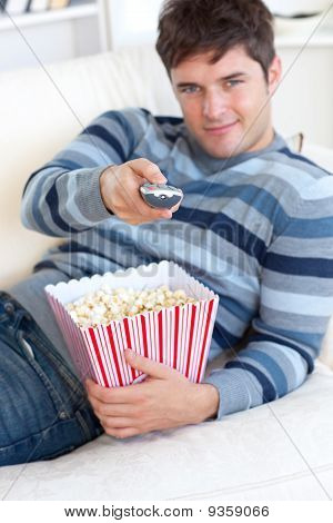 Relaxed Young Man Eating Popcorn And Holding A Remote Lying On The Sofa