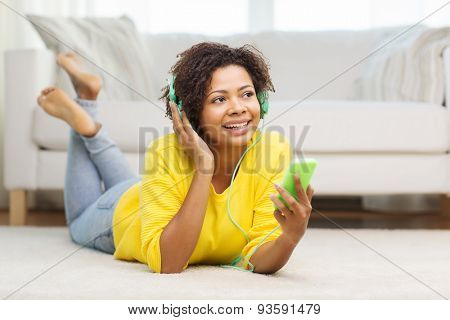 people, technology and leisure concept - happy african american young woman lying on floor with smartphone and headphones listening to music at home poster