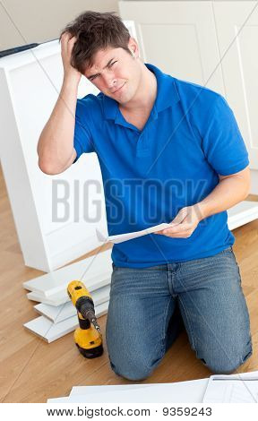Incomprehensive Caucasian Man Reading The Instructions To Assemble Furniture In The Kitchen