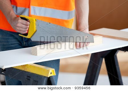 Close-up Of A Male Worker Sawing A Wooden Board