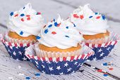 Cupcakes with patriotic 4th of July sprinkles on vintage background shallow depth of field poster