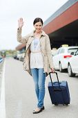 travel, business trip, people and tourism concept - smiling young woman with travel bag over taxi at airport terminal or railway station poster