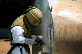 Worker is removing paint by air pressure sand blasting poster