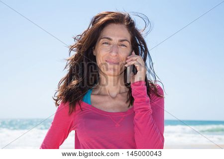 Portrait Pink Shirt Woman Talking On Mobile Sea Behind