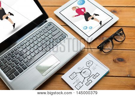 sport and technology concept - close up of on laptop computer and tablet pc with fitness application on screens, notebook and eyeglasses on wooden table