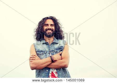 subculture, youth culture and people concept - smiling young hippie man in demin vest