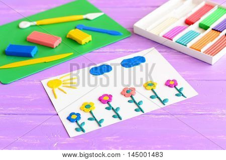 Card with plasticine flowers, sun and clouds. Plasticine set on a wooden table. Children modeling clay art. Crafts idea for development of fine motor skills in children