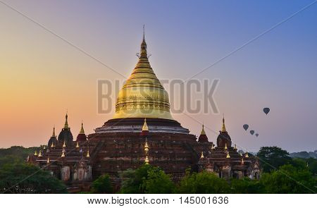 Dhammayazika pagoda in misty morning light in Bagan. This Dhammayazika  pagoda gilded with Bagan gold leaves is ancient and most visited in Bagan. It is located east of Bagan, Myanmar.