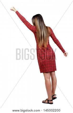 Back view of business woman. Raised his fist up in victory sign. Raised his fist up in victory sign. The girl in red plaid dress spreading his hands apart.