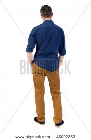 Back view of man . Standing young guy. man in a blue shirt with the sleeves rolled up, standing with his hands in his pocket, and looks into the distance.