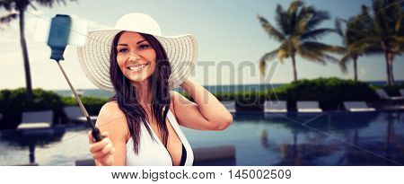 lifestyle, leisure, summer, technology and people concept - smiling young woman in sun hat taking picture with smartphone on selfie stick over resort beach with palms and swimming pool background