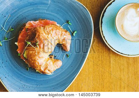Beakfast with croissant with salmon and coffee