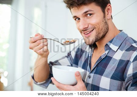 Portrait of happy young man in checkered shirt eating cereals with milk at home