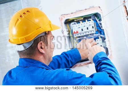 electrician with screwdriver repair switching electric actuator in fuse box