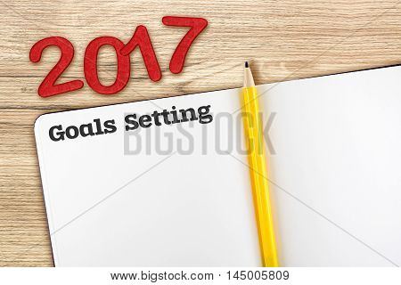 Top View Of 2017 New Year Red Number With Blank Open Notebook And Yellow Pencil On Wooden Table Top,