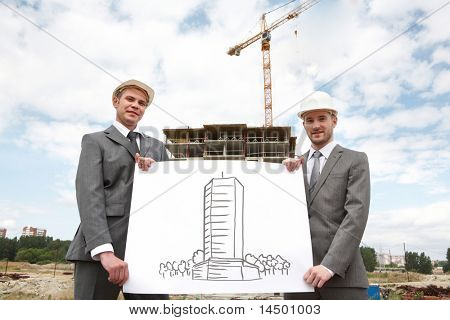 Portrait of two successful builders holding large sheet of paper with scheme of construction on it