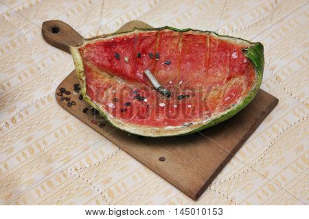 Moulded watermelon and cigarette but leftovers on a plain matress fabric, close-up.