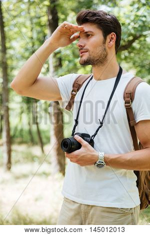 Handsome young man photographer holding modern photo camera and looking far away in forest