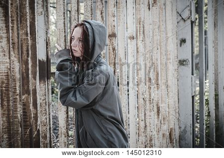 sad young girl in the old dirty clothes standing at the iron fence and sadly looks through it. Homeless devshuka. A homeless teenager.