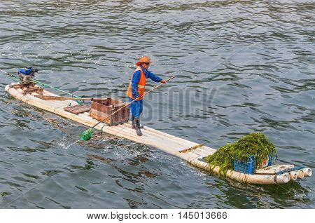 Yangshuo China - October 20 2013: Worker are collecting and removing algae on his bamboo raft from the Li River near Yangshuo China.