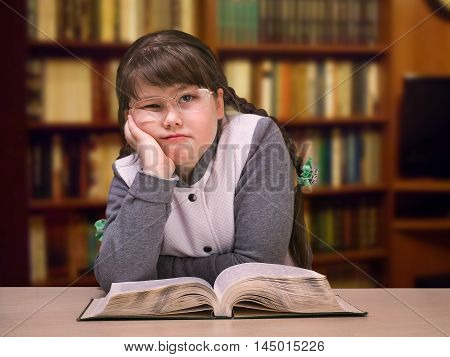 The girl in the library with a book and glasses. The concept of overweight teenage complexes difficulties at school