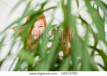 Red-haired woman smiling through blurred green foliage