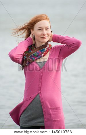 Outdoor portrait of a beautiful redhead woman with flying hair