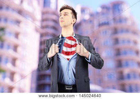 Yong businessman showing USA flag under suit on blurred building background.