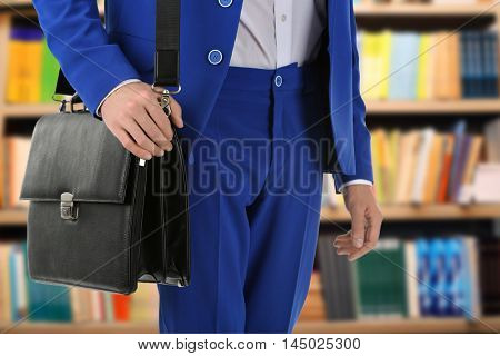 Businessman with bag on blurred bookshelves background. Law concept.