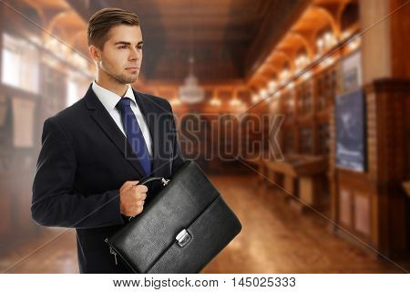 Businessman holding briefcase on blurred hall background. Law concept.