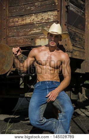 Portrait of young shirtless cowboy with sexy body, jeans and hat posing against of old train while looking at camera