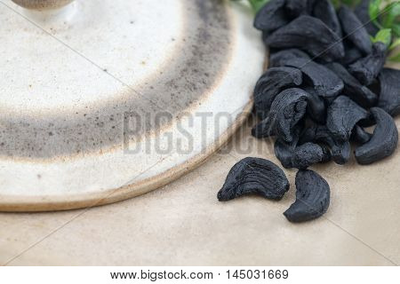 Selective focus Close up of Black Garlic cloves latest wonder food rich in antioxidants vitamins and minerals. with a stone wear background and a small amount of greenery