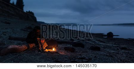 Hiker sitting by the bonfire on river shore. Focus on the bonfire and feet