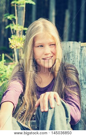 Mischievous little blond girl posing in a pine forest on a sunny morning. Toned image