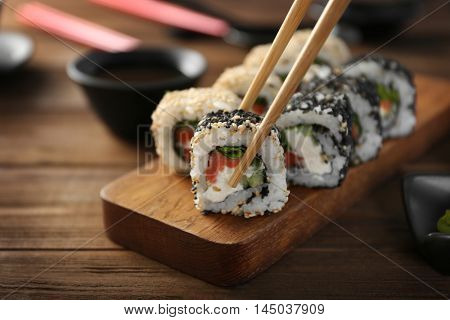 Tasty sushi roll with wooden chopsticks, closeup