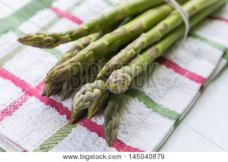 Close up of fresh asparagus bunch arranged on stripped kitchen cloth