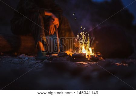 Person warms their feet next to a campfire at dusk camping in the woods.