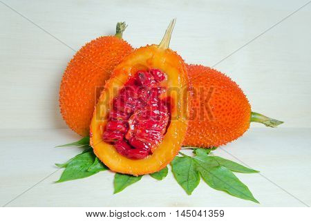 Gac Fruit, Typical Of Orange-colored Plant Foods In Asia With Half Cross Section Isolated On Wood
