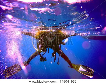 A scuba diver floating on the surface without the regulator. View of the scuba diver gear fins mask bcd and bubbles underwater in the deep blue sea of Limassol Cyprus.