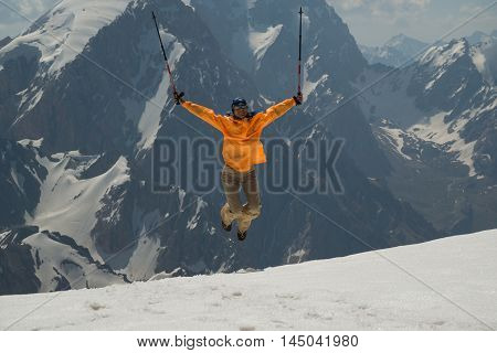 Mountain travel. Woman jumps and lifts her arms in victory. Woman dressed in orange windbreaker.