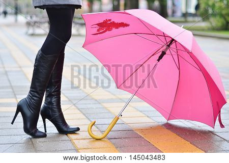 umbrella and femail black boots on the wet street