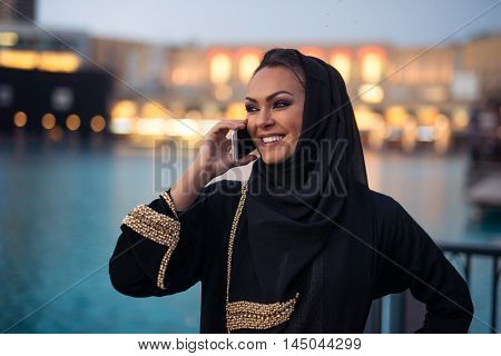 Beautiful musilm woman talking on a mobile phone.