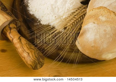 Detail of a rural kitchen with loaf of bread, wheat ears, white flour and rolling pin.