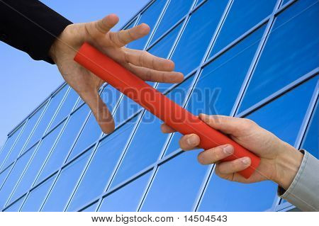 One businessman passing a red baton to another businessman over blue office building. Symbol of teamwork, helping and partnership.