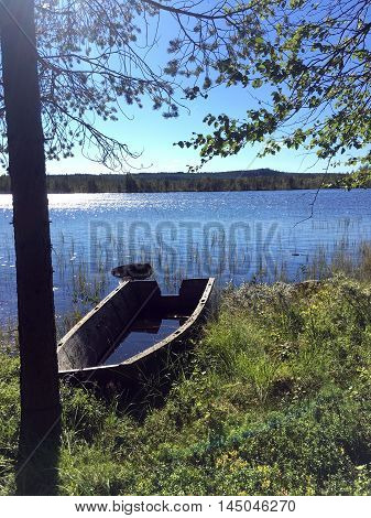 Old skiff on the shoreline of a little lake in the North of Sweden