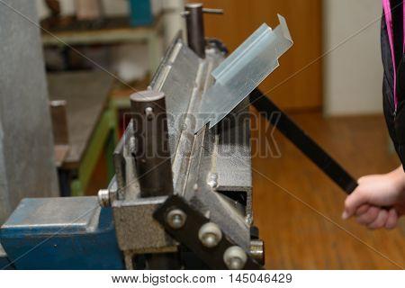 Craftswoman processed sheet on a metal bender