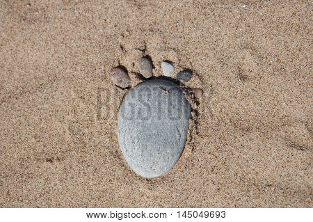 Six rocks in sand in the shape of a footstep