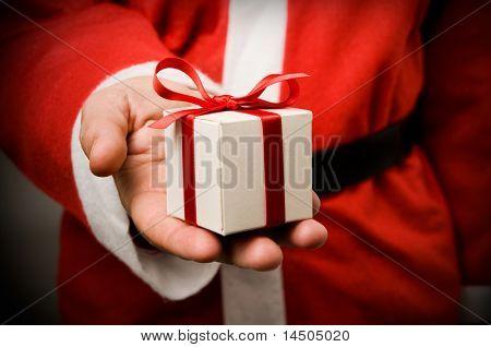 Santa Claus holding und bietet ein Geschenk auf seine Hand.