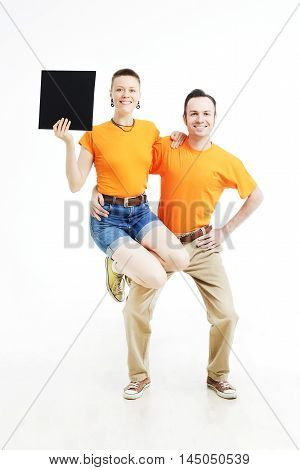 Young couple with sign they are holding against a white background. Young girl is holding a sign and astride. Young couple are wearing in orange T-shirts with sign in a hand.
